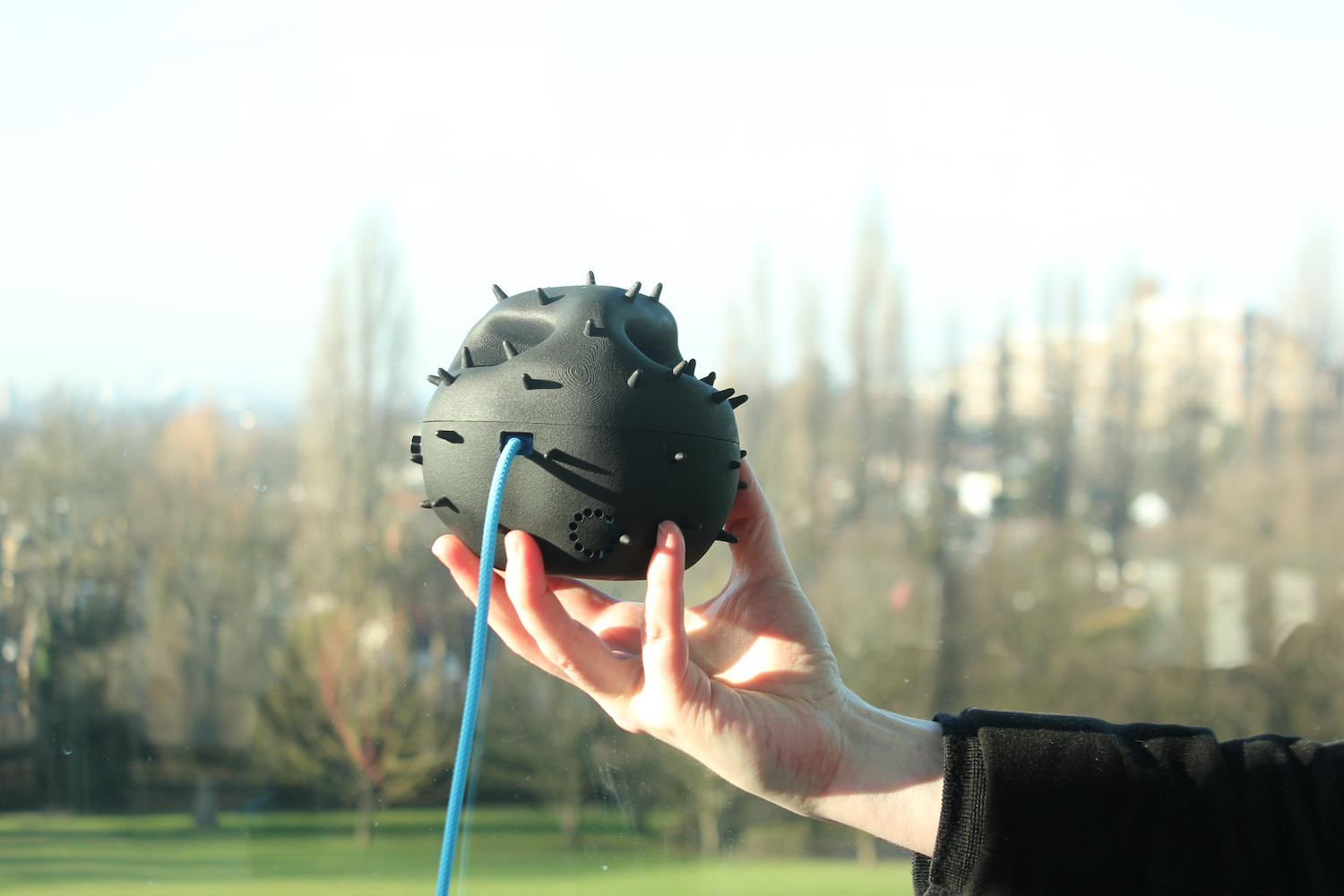 A pollen Dustbox 2.0 held up by a hand overlooking London from the Horniman museum
