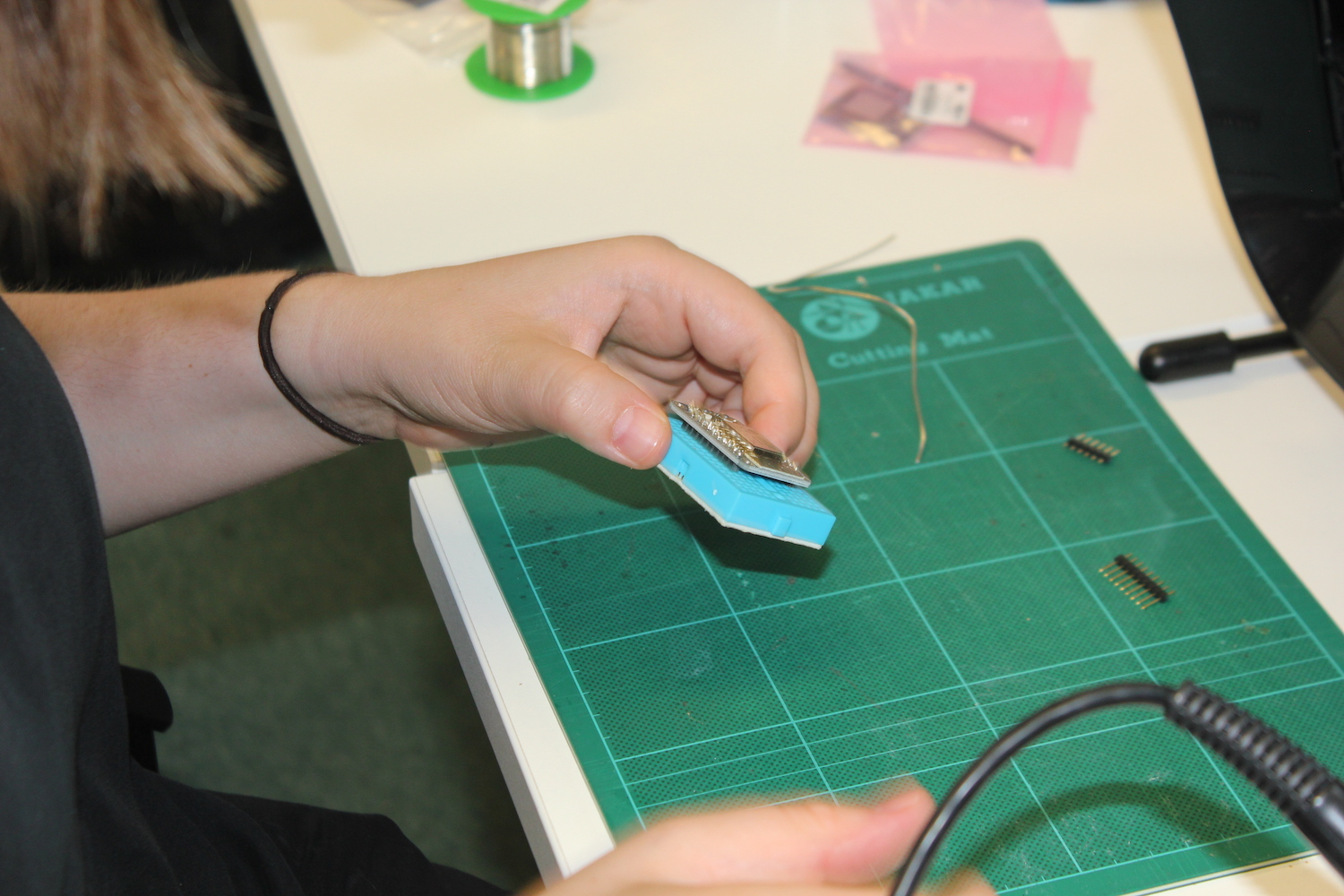 A researcher holds a small breadboard containing the Adafruit Huzzah ESP8266 Breakout to pin headers in one hand as she prepares to solder