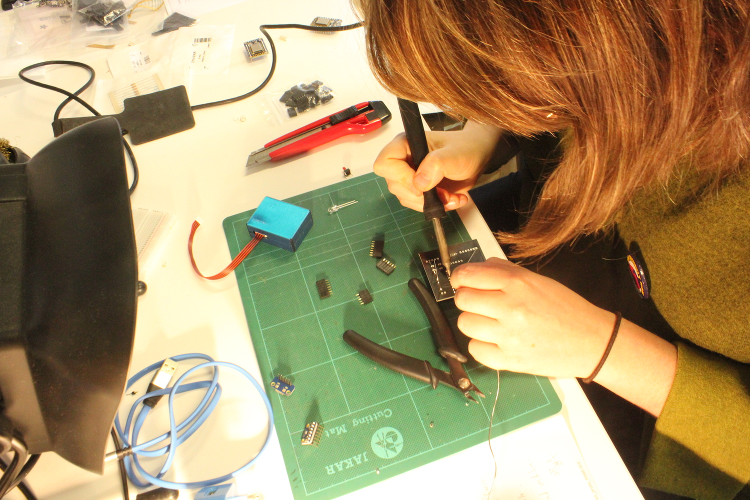 A researcher holds a soldering iron in her hand as she solders parts to the Dustbox 2.0 PCB